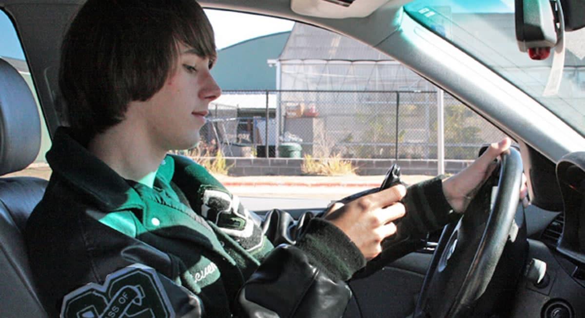 Joven manejando y usando telefono