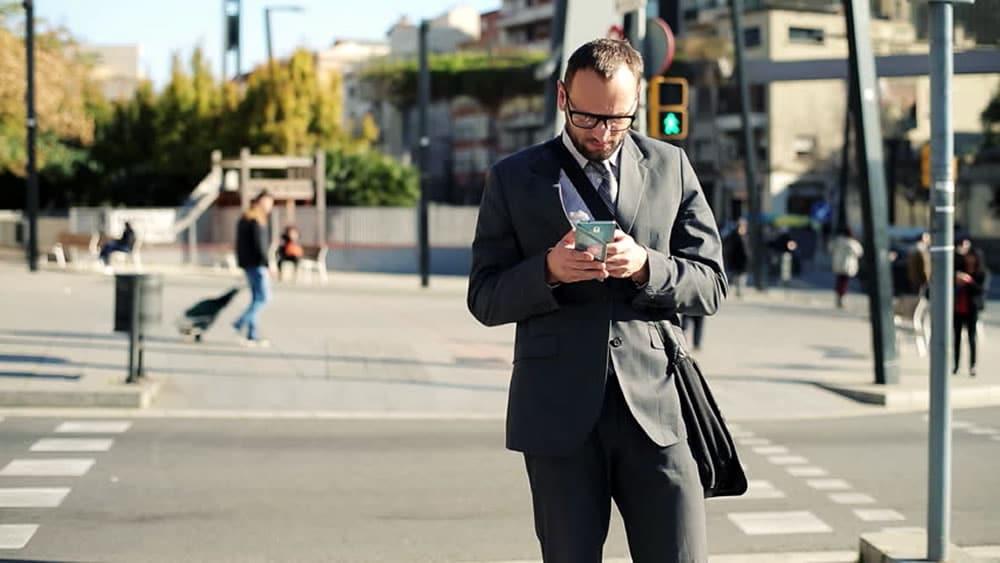 Cruzando la calle mirando el celular.